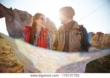 Lens flare image of joyful young tourist couple looking at each other while holding big map at hike in mountains on sunny day