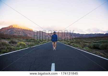 Portrait of man in blue jacket standing straight in the middle of road on mountains background, Tenerife Island
