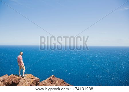 Young male traveler standing on cliff edge and looking at vast blue ocean during summer vacation on Tenerife
