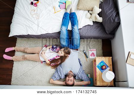 Family of two having nap together: bearded dad in casualwear sleeping on carpet while his little daughter putting head on his belly with closed eyes