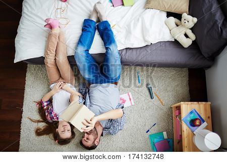 Teenage girl and her middle-aged father lying on messy bedroom floor and watching photo book, feet up on bed