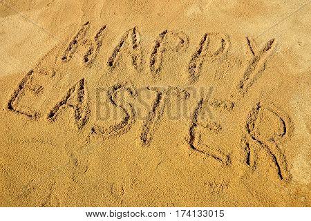 Message Happy Easter handwritten on the golden sandy beach