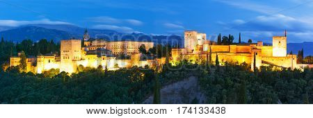 Panorama of Moorish palace and fortress complex Alhambra with Comares Tower, Alcazaba, Palacios Nazaries and Palace of Charles V during evening blue hour in Granada, Andalusia, Spain