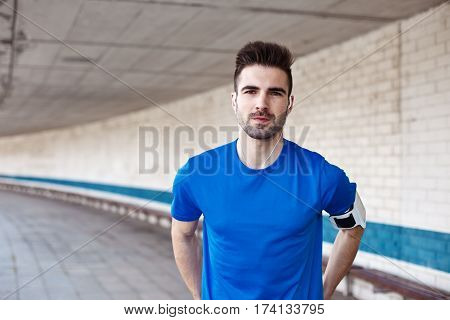 portrait of young handsome athlete with stubble outdoors