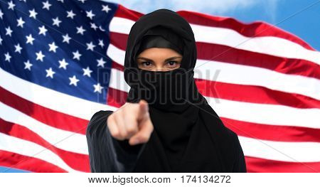 immigration and people concept - muslim woman in hijab pointing finger to you over american flagbackground