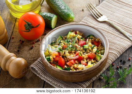 Traditional Israeli healthy meal Ptitim with tomatoes cucumber and onion for delicious healthy breakfast. Classic Moroccan couscous with vegetables. Top view.