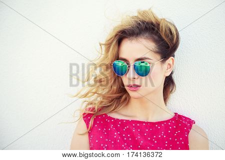 Portrait of Beautiful Fashion Woman in Sunglasses. Trendy Romantic Girl in Summer. Stylish Lovely Female. White Wall Background Copy Space. Not Isolated Toned Photo.