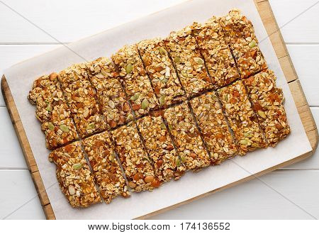 Homemade no bake granola bars with oat flakes honey dried apricots and seeds on white baking paper. Healthy energy cereal snacks on wooden background.