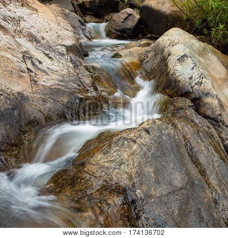 A mountain river waterfall scene with large boulders in Vietnam.