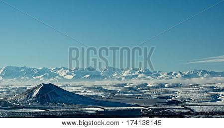 Beautiful Mountain Peaks of Caucasus Range against Blue Sky in Sunny Winter Day Outdoors