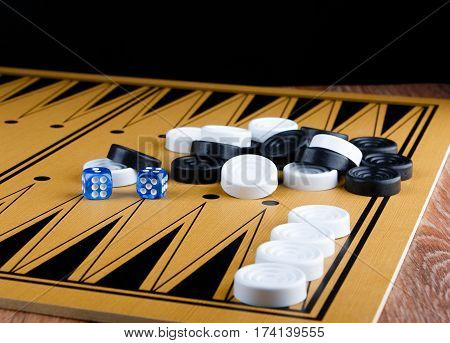 pile of checkers and blue dices on backgammon board