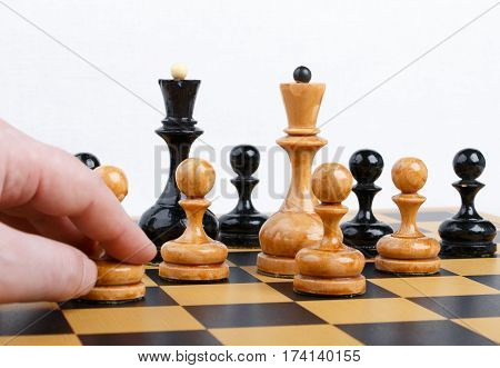 man making the white pawn move in a chess game on white background