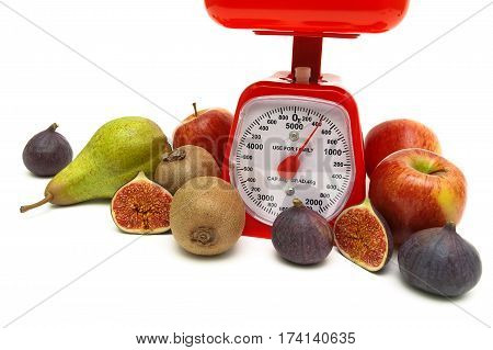 kitchen scales and ripe fruits on white background. horizontal photo.