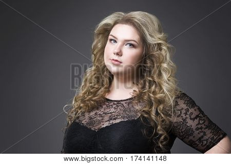 Young beautiful blonde plus size model in black dres xxl woman portrait on gray studio background makeup and hairstyle