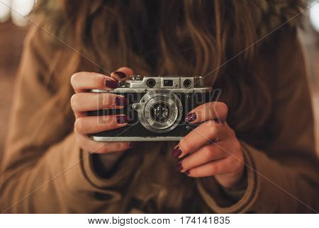 Hipster girl with retro camera taking photos in the night city street