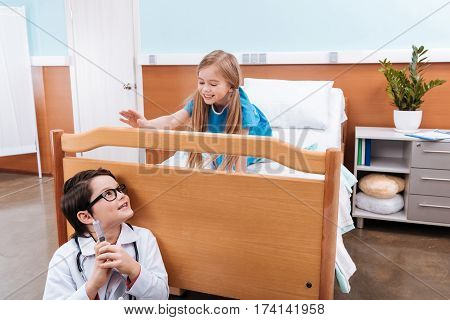 Smiling boy doctor with syringe playing with little girl patient in hospital