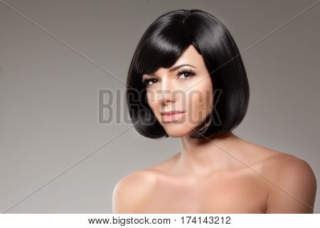 Stylish woman with a bob hairstyle. Girl model with a short black fringe and vlosami.