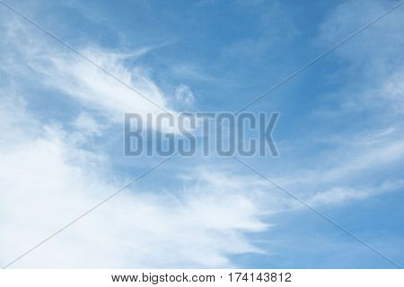 White streaks of clouds on a bright blue sky sunny summer day horizontal image