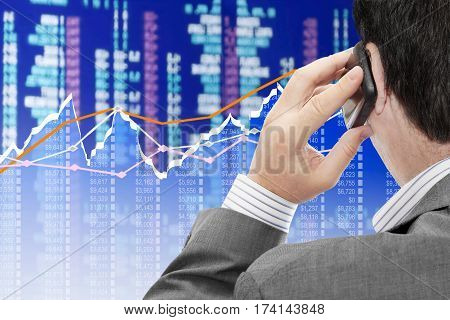 Man on a phone analyzing financial data and charts