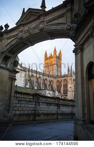 Bath cathedral framed through archway in golden late evening sunlight