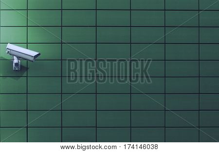 Horizontal front view of a surveillance monitoring white camera viewed from a side with green background wall of metallic plates copyspace on the right