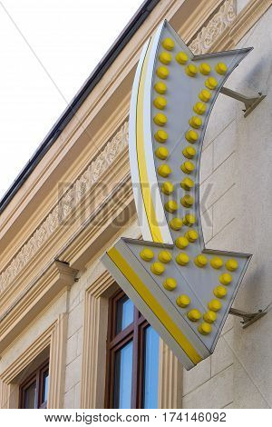 vertical front view of arrow vintage light bulb sign pointing down on a building with classical architecture