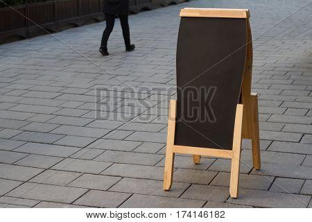 horizontal blank black wooden restaurant sidewalk chalkboard on a street with people passing by