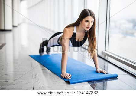 Working her core muscles. Full length of young beautiful woman in sportswear doing plank while standing in front of window