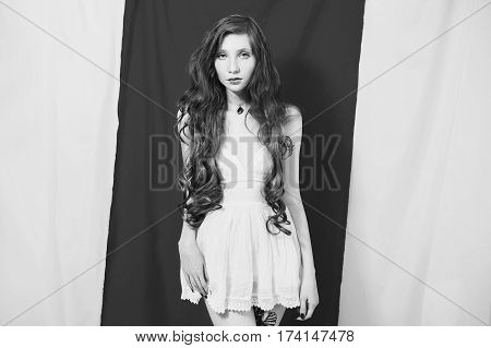 Black and white art photography monochrome girl with slim waist in a white dress on a white background. Fetish model.