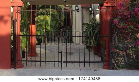 Gated entryway with pink flowers, Cancun, Mexico.