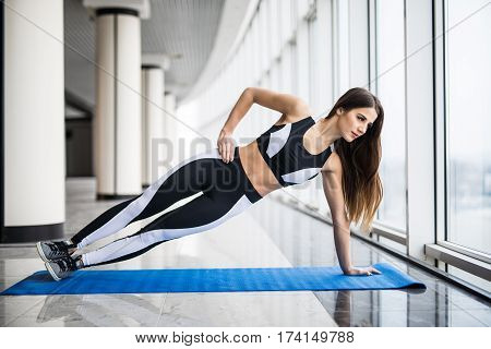 Confident side plank. Full length of young beautiful woman in sportswear doing side plank in front of window at gym
