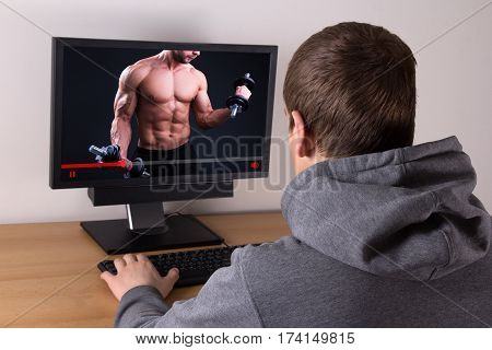 young man watching sport video blog online at home