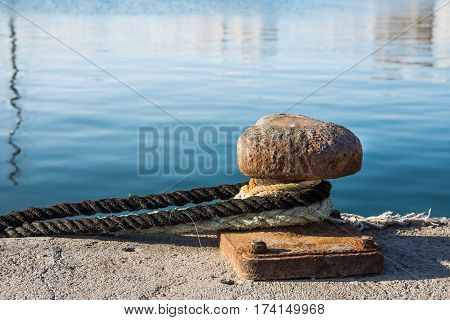 Rusty mooring bollard with tied lines or ropes at waterfront sunny day mediterranean Spain Torrevieja port