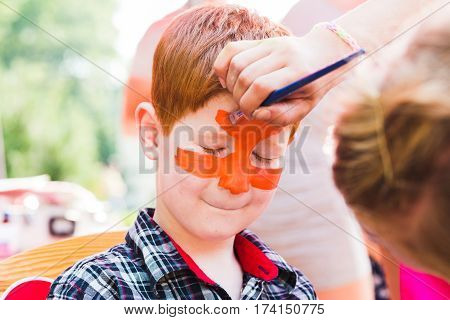 Face art for little boy. Tiger eyes painting. Children birthday party entertainment, artist making funny makeup