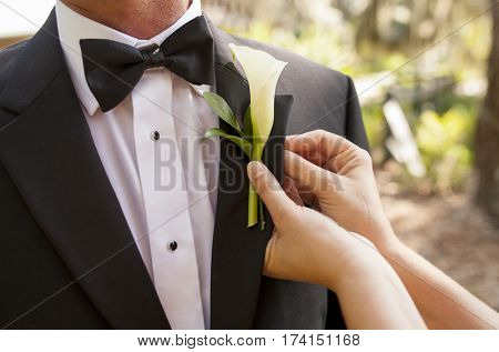Closeup of hands pinning boutonniere on groom