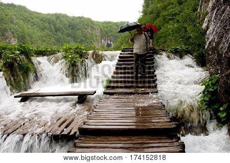 PLITVICE LAKES, CROATIA, MAY 16, 2010: Tourists walking in the rain on slippery boardwalk