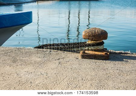 Rusty mooring bollard with tied lines at waterfront blue boat stern mediterranean Spain Costa Blanca