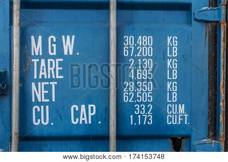 Rusty blue container with weights and dimensions informations