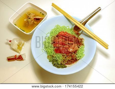 Dry jade noodle duck served with boiled pork bones soup in cup Lighting to soft and warm tone on white background Concept is in a private room This menu set sale for one person breakfastor dinner.
