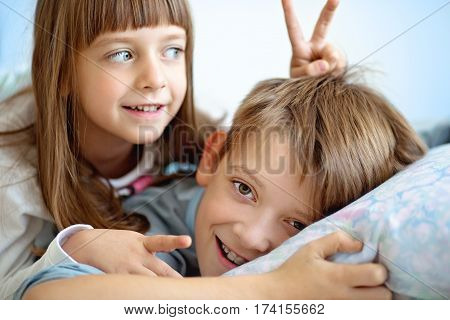 cute kids brother with sister waking up in bed at home
