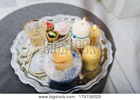 Candles cake pearls on a silver platter during the wedding.