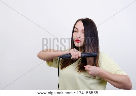 woman in a yellow t-shirt with a rectifier for hair
