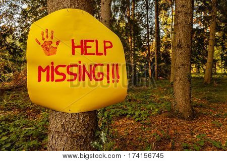 help the missing sign hanging on a tree woods /a sign reading help missing
