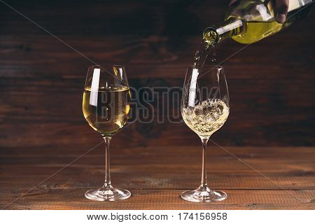Two Glasses Pouring White Wine From A Bottle In A Wineglass On Wooden Background