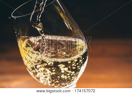 Pouring White Wine From A Bottle In A Wineglasses On Wooden Background. Free Space