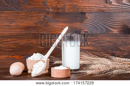 Natural Homemade Products: Milk, Cheese, Sour Cream And Eggs On Old Wooden Background With Ears Of W
