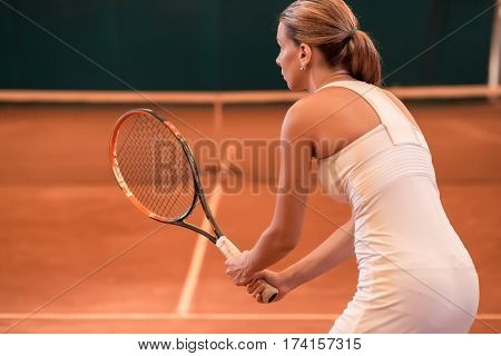 View from the back on a female tennis player wearing a sportswear playing tennis on a court indoor