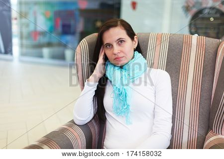 The Woman In A Turquoise Scarf Sits In A Chair