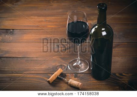 Bottle Of Red Wine And Glass, Corkscrew And Corks On Wooden Table