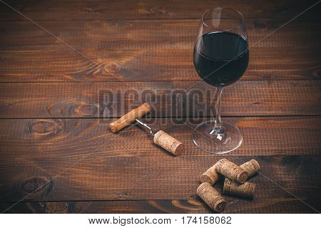 Glass Of Red Wine, Corkscrew And Corks On Wooden Table